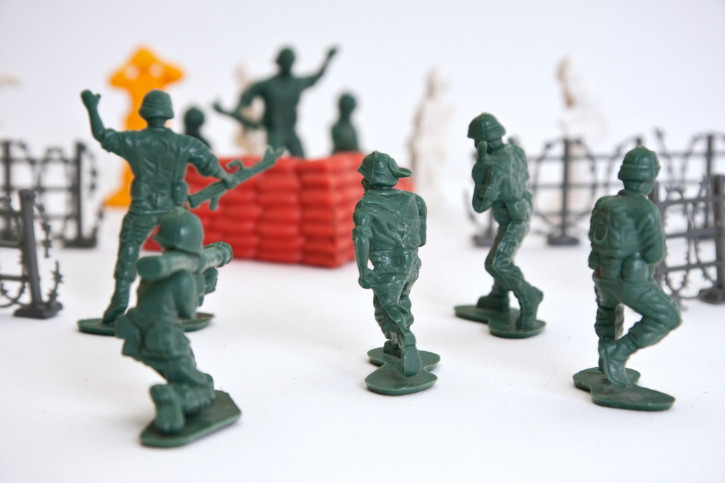 A bunch of green toy soldiers staging a combat scene, trying to destroy the enemy's defenses. The plastic figurines represent several different army men from World War II, heading towards some barbwire fences and a mock-up orange wall.